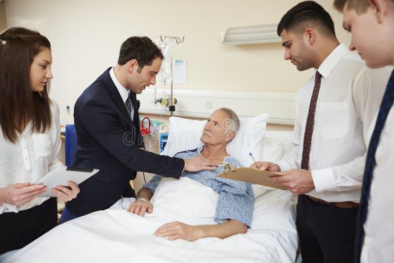 Medicinsk personal på rundor som står vid manlig patients säng royaltyfri fotografi