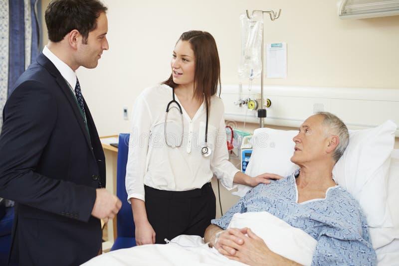 Medicinsk personal på rundor som undersöker den höga manliga patienten arkivbilder