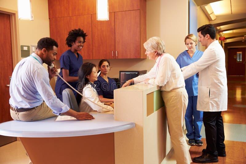 Medicinsk personal på upptagen sjuksköterskas station i sjukhus royaltyfri foto