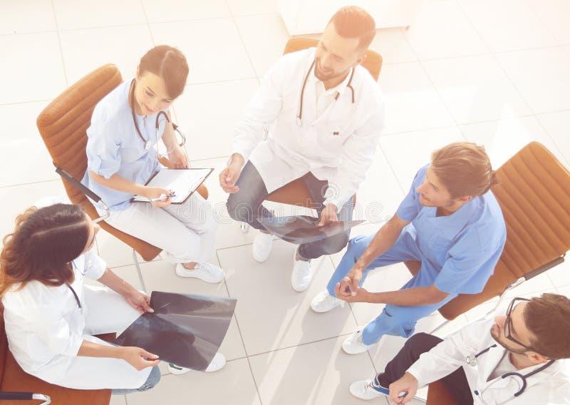 Medicinsk personal som diskuterar arbetsplanet med patienterna royaltyfri fotografi