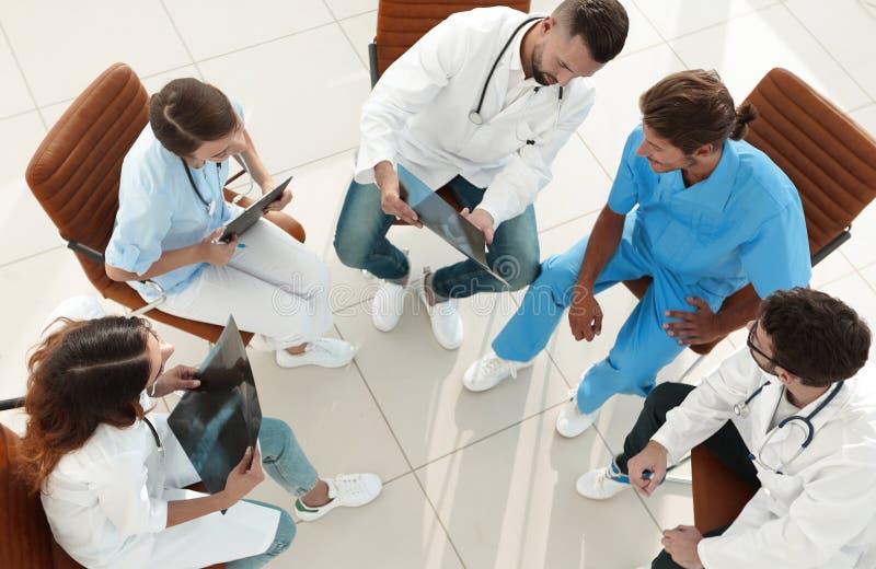 Medicinsk personal som diskuterar arbetsplanet med patienterna arkivfoton