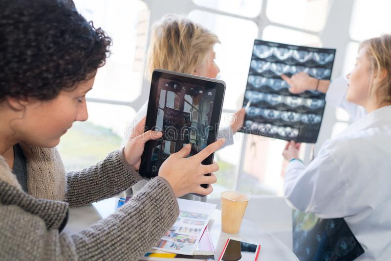 Medicinsk personal som ser röntgenstrålar och minnestavlaskärmen royaltyfri fotografi