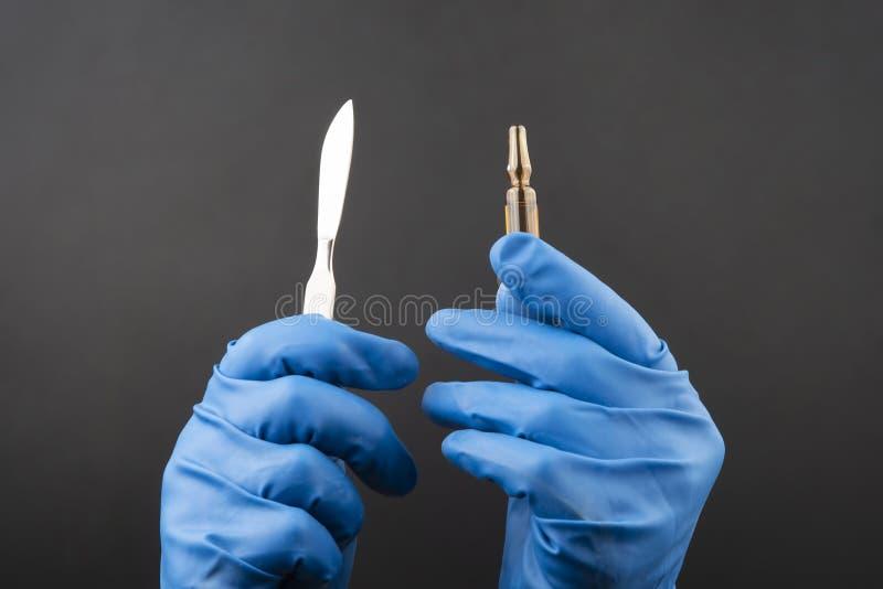 Medicinsk skalpell och liten medicinflaska för injektion i händer som bär blåa handskar royaltyfri foto
