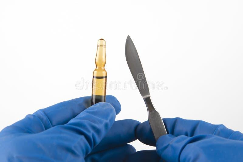 Medicinsk skalpell och liten medicinflaska för injektion i händer som bär blåa handskar royaltyfria foton