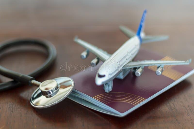 Medicinsk stetoskop, pass och ett flygplan Globalt sjukvård- och loppförsäkringbegrepp arkivbilder