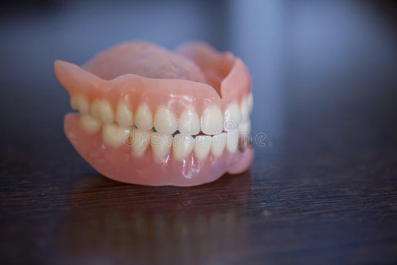Medicinsk tandprotes på trätabellen fotografering för bildbyråer