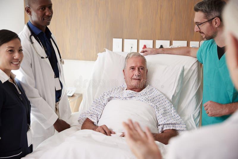 Medicinsk Team On Rounds Meeting Around säng av den höga manliga patienten arkivfoton