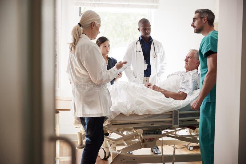 Medicinsk Team On Rounds Meeting Around säng av den höga manliga patienten royaltyfri bild