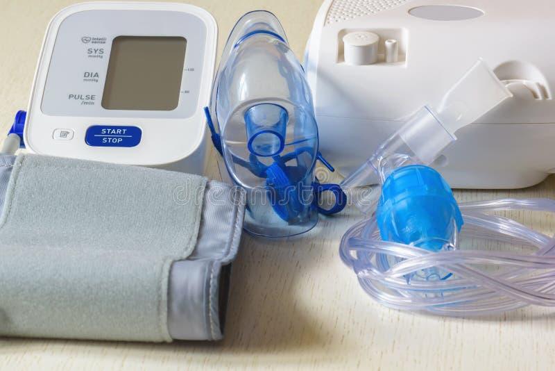 Medicinsk utrustning för inandning med en respiratorisk maskering, en nebulizer och blodtryckmätning royaltyfria foton