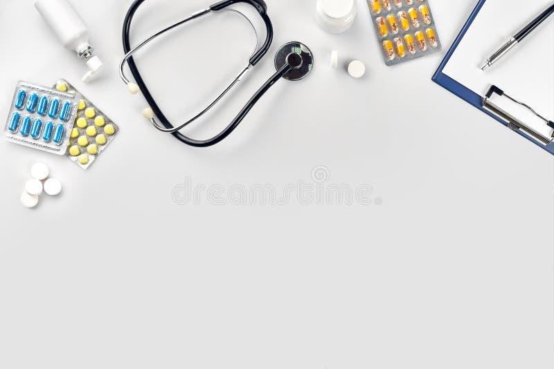 Medicinsk utrustning: preventivpiller-, stetoskop- och vitmellanrum med en penna på vit bakgrund Top beskådar kopiera avstånd royaltyfria foton
