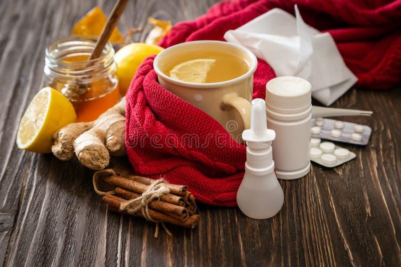 Medicinsk vårdbegrepp - ljust rödbrun honung- och citronte med droger, preventivpillerar och sprej arkivbild