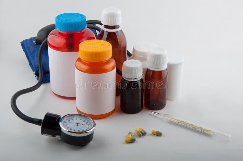 Medicinsk visartavlatonometer, termometer, preventivpillerar och flaskor royaltyfri foto