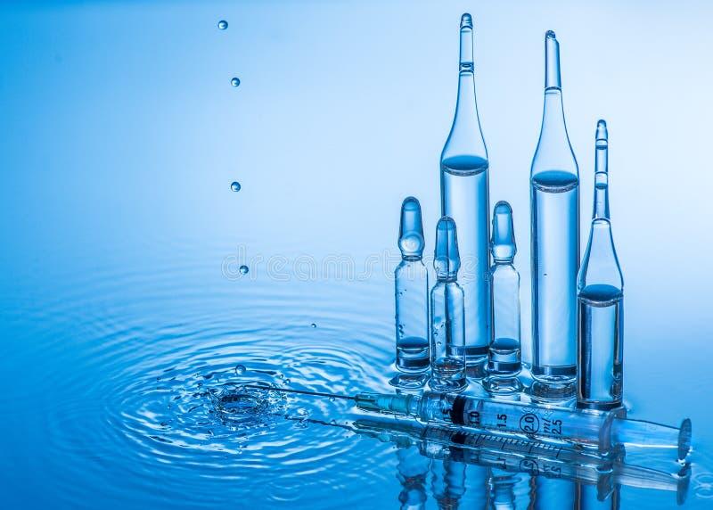 Medicinska ampuller och injektionsspruta på bakgrund för blått vatten med färgstänk och droppar royaltyfri fotografi