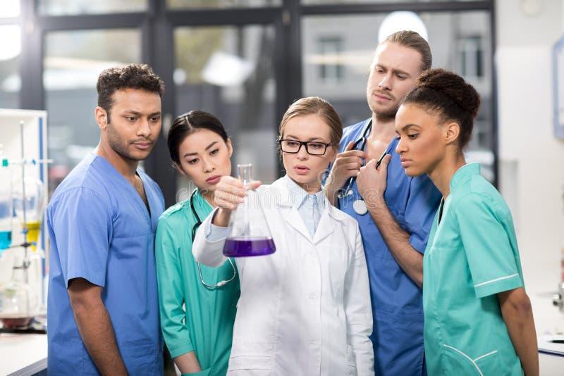 Medicinska arbetare som analyserar provröret i laboratorium arkivfoto