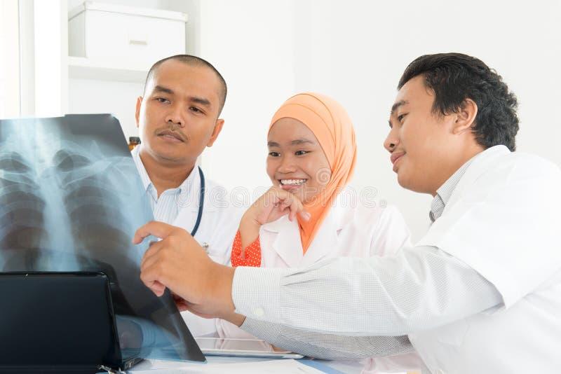 Medicinska doktorer som diskuterar på röntgenstrålebildläsning arkivfoto