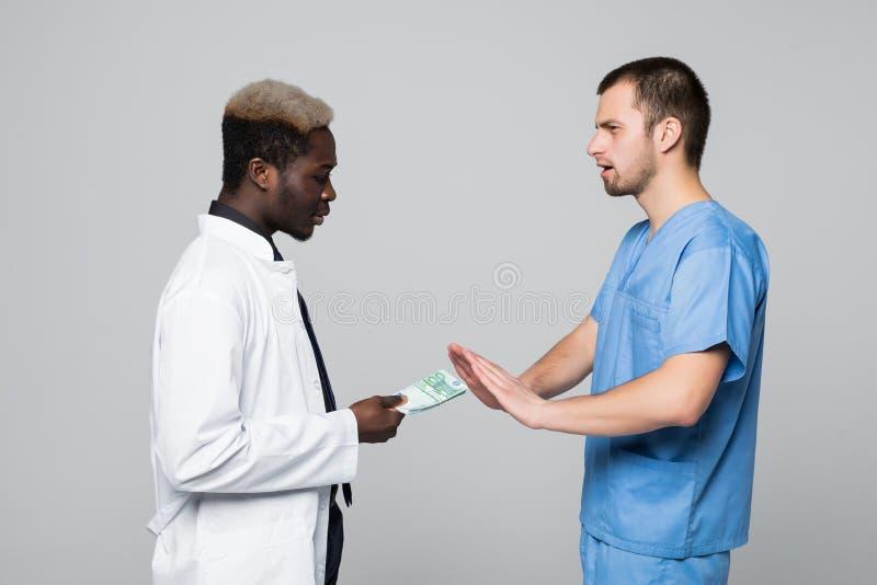 Medicinska kirurgavskräden som muter pengar från doktorn som isoleras på grå bakgrund arkivbilder