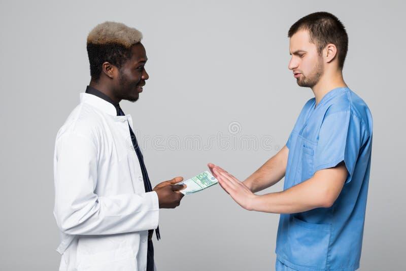 Medicinska kirurgavskräden som muter pengar från doktorn som isoleras på grå bakgrund royaltyfri bild