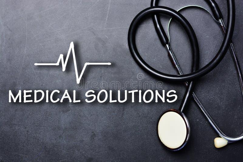 Medicinska lösningar smsar på svart tavla med stetoskop- och hjärtslaghastighet fotografering för bildbyråer