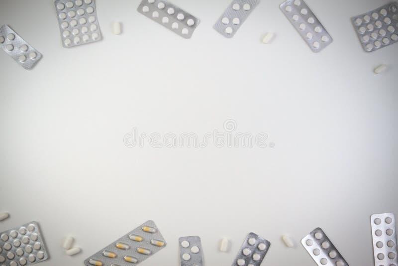 Medicinska minnestavlor, kapslar och preventivpillerar i ram för blåsapacke som bakgrund med kopieringsutrymme för text eller bil arkivbilder