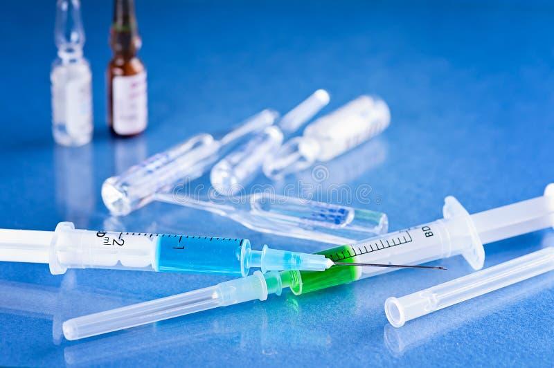 Medicinska små medicinflaskor för injektion med en injektionsspruta som isoleras på blå bakgrund royaltyfria bilder