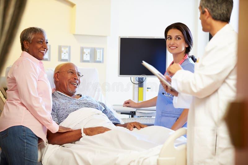 Medicinska Team Meeting With Senior Couple i sjukhusrum arkivbild