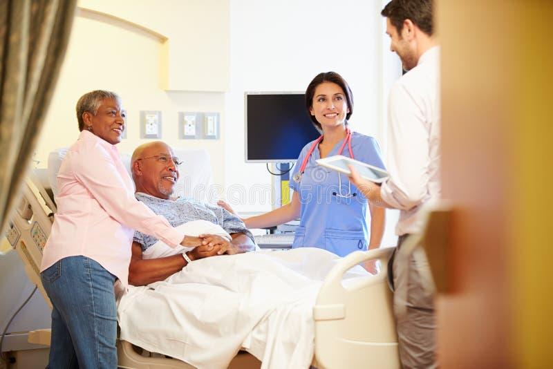 Medicinska Team Meeting With Senior Couple i sjukhusrum royaltyfri foto