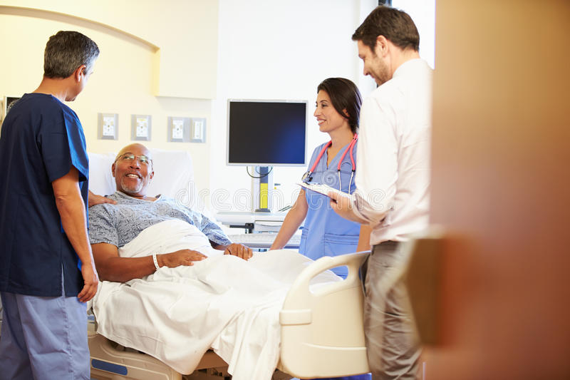 Medicinska Team Meeting With Senior Man i sjukhusrum arkivbilder