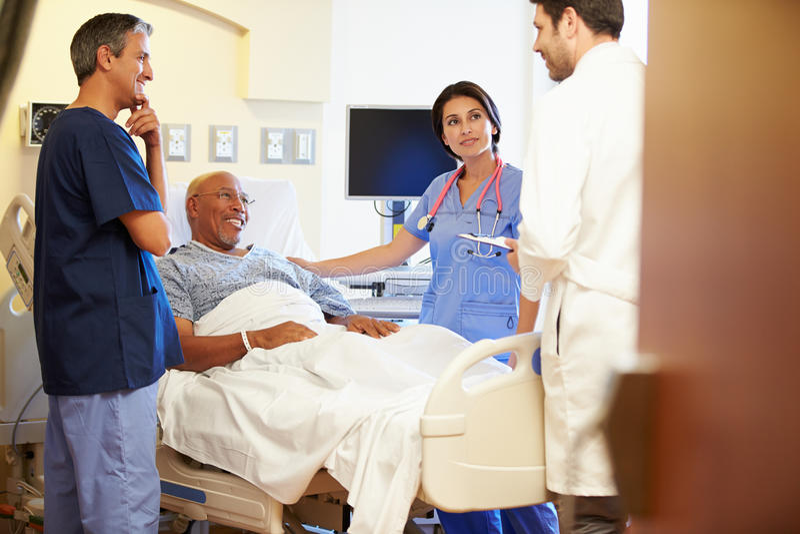 Medicinska Team Meeting With Senior Man i sjukhusrum arkivfoto