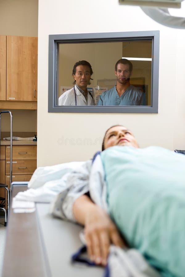 Medicinska Team Monitoring Patient Getting Xray royaltyfria bilder