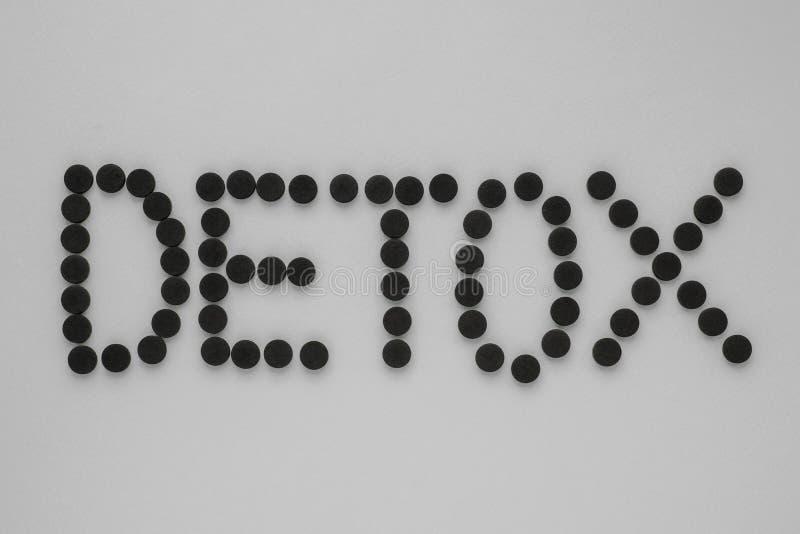 Medicinskt aktiverat kol i form av en inskrift'detoxs på en grå bakgrund B?sta sikt, kopieringsutrymme royaltyfria bilder