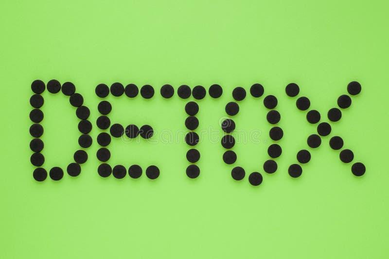 Medicinskt aktiverat kol i form av en inskrift'detoxs på en grön bakgrund B?sta sikt, kopieringsutrymme arkivbilder