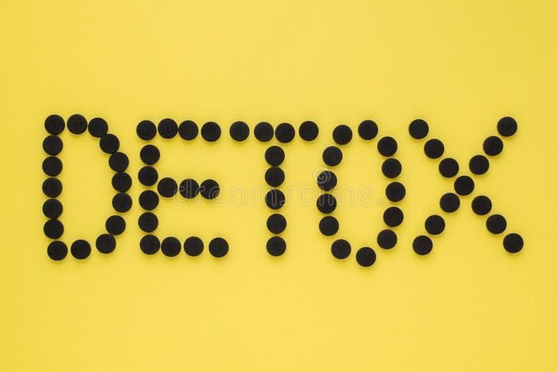 Medicinskt aktiverat kol i form av en inskrift'detoxs på en gul bakgrund B?sta sikt, kopieringsutrymme arkivbilder