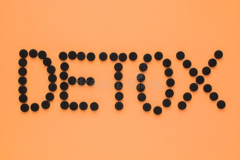 Medicinskt aktiverat kol i form av en inskrift'detoxs på en orange bakgrund B?sta sikt, kopieringsutrymme royaltyfri foto