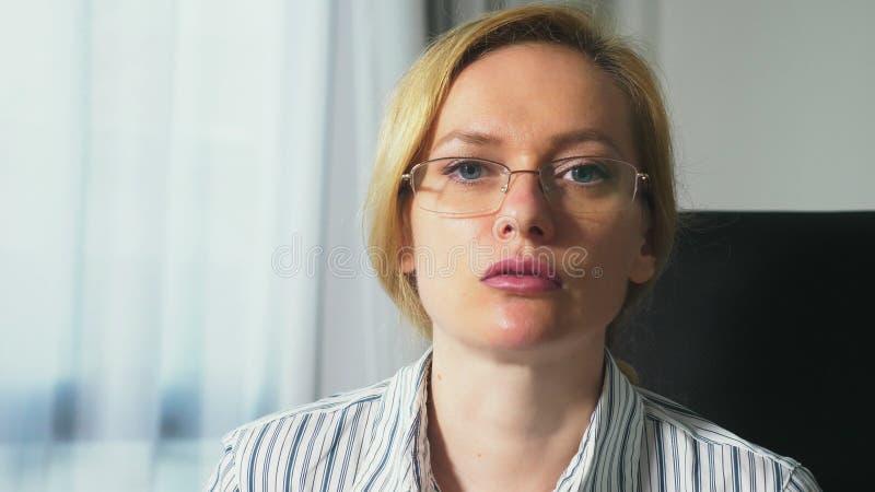 Medicinskt begrepp med ett besök till en psykolog, närbild, stående av en kvinna med exponeringsglas, som säger något, a arkivbilder