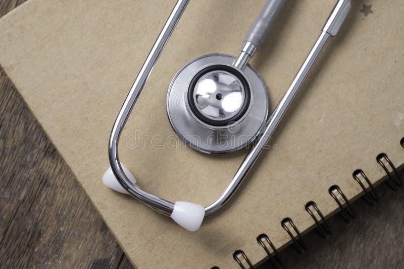 Medicinskt begrepp: stetoskop på anmärkningsboken med wood bakgrund royaltyfria bilder