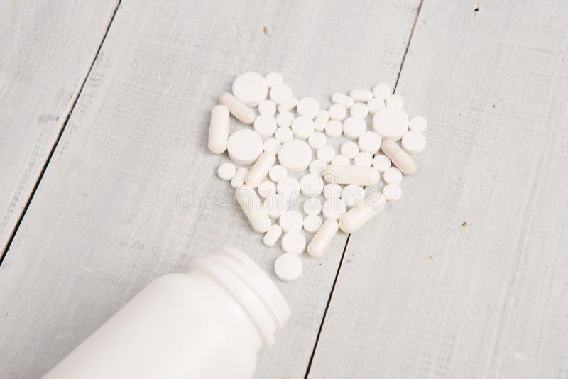 Medicinskt begrepp - vit hjärta av preventivpillerar och kapslar royaltyfria foton