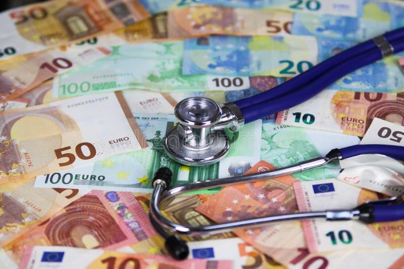 Medicinskt kostat begrepp - stetoskop på sedlar för europapperspengar royaltyfri foto
