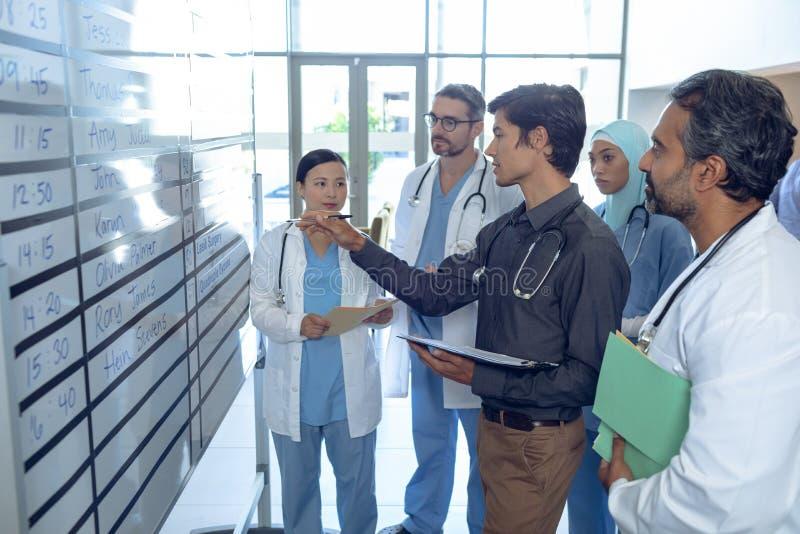 Medicinskt lag av doktorer som diskuterar deras förskjutningar på diagram på sjukhuset arkivbilder