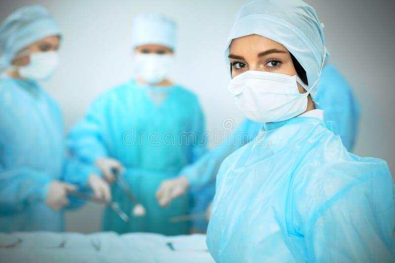 Medicinskt lag i maskeringar som utför operation Fokus på kvinnlig doktors- eller allmäntjänstgörande läkareflicka Medicin nöd- h royaltyfri bild