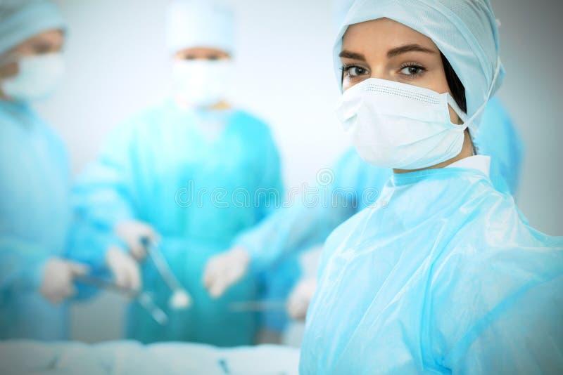 Medicinskt lag i maskeringar som utför operation Fokus på kvinnlig doktors- eller allmäntjänstgörande läkareflicka Medicin nöd- h arkivfoto