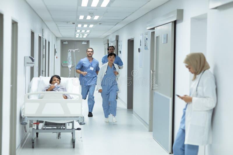 Medicinskt lag som kör i korridoren på sjukhuset fotografering för bildbyråer
