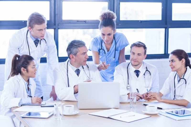 Medicinskt lag som ser in i bärbara datorn och har en diskussion royaltyfria foton