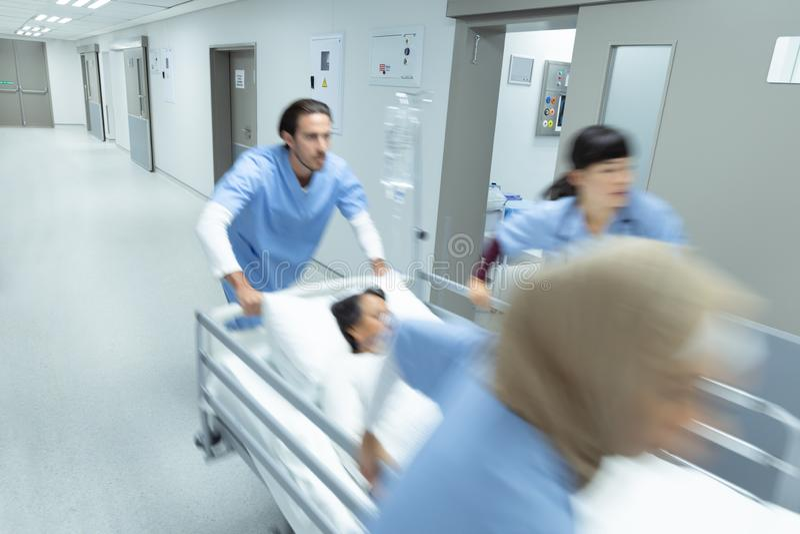 Medicinskt lag som skjuter nöd- bårsäng i korridor royaltyfri bild