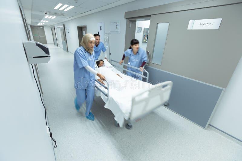 Medicinskt lag som skjuter nöd- bårsäng i korridor arkivfoto