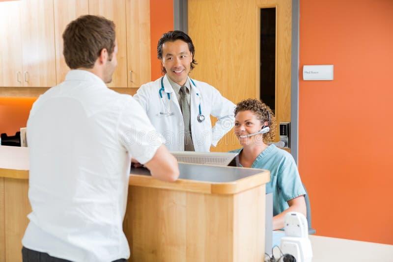 Medicinskt Team With Patient At Reception skrivbord fotografering för bildbyråer