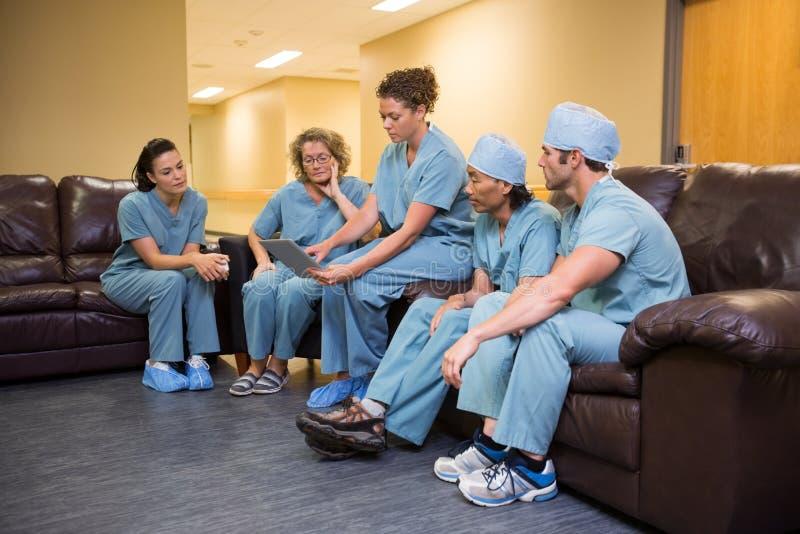 Medicinskt Team Using Digital Tablet In sjukhus arkivbilder