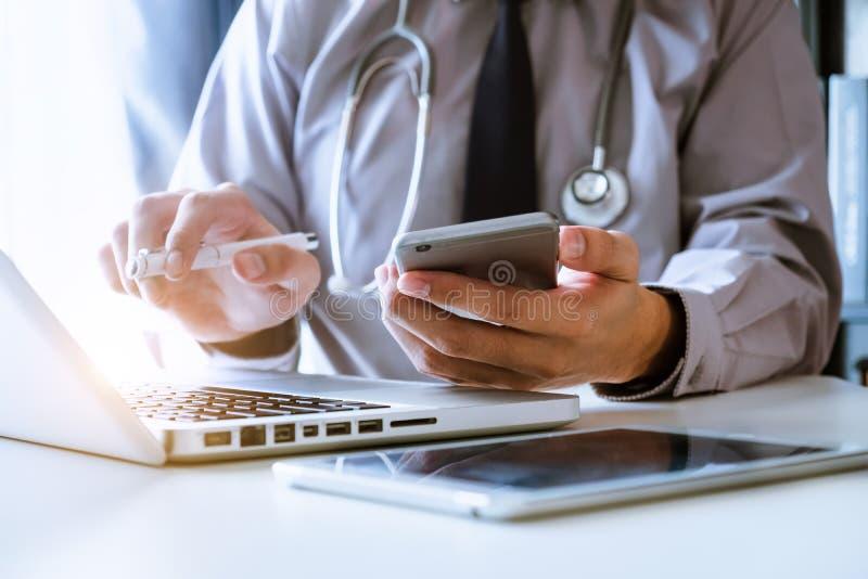 Medicinskt teknologibegrepp Doktor som arbetar med mobiltelefonen och stetoskopet i modernt kontor arkivbild
