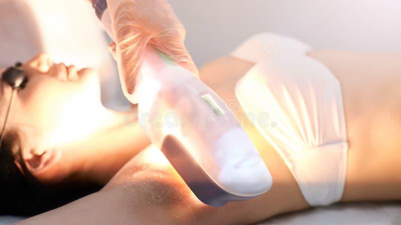 Medicinskt tillvägagångssätt för skönhetlaser-cosmeology Ung kvinnlig på salongen Yrkesmässig doktor Kvinnaskincareteknologi Hårb royaltyfria foton