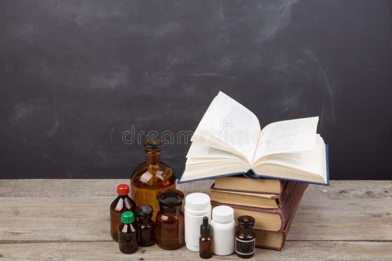 Medicinskt utbildningsbegrepp - b?cker, apotekflaskor, stetoskop i salongen med svart tavla arkivfoto