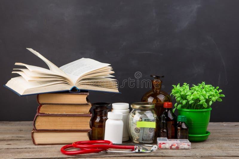 Medicinskt utbildningsbegrepp - pengarexponeringsglas, b?cker, apotekflaskor royaltyfri foto